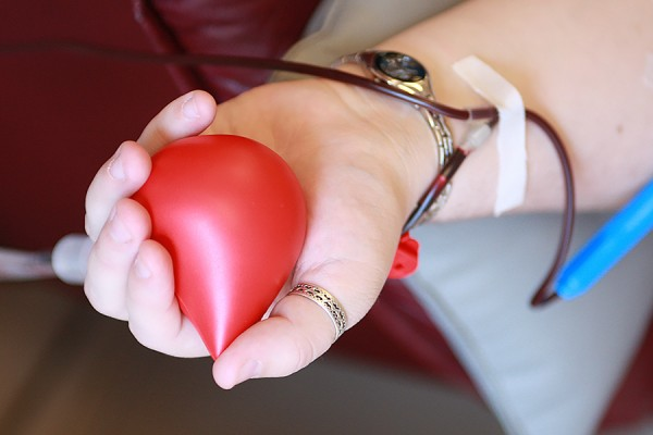 hand of blood donor holding red drop-shaped squeeze toy