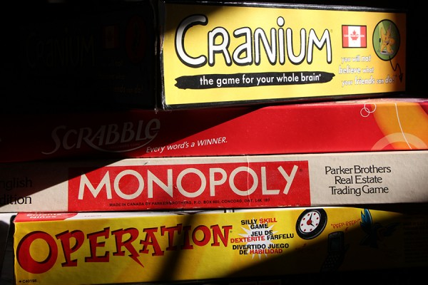 stacked game boxes: Cranium, Scrabble, Monopoly, Operation