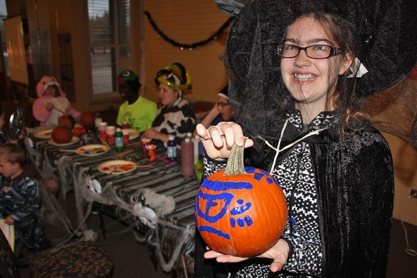 Kid dressed as witch displaying painted pumpkin