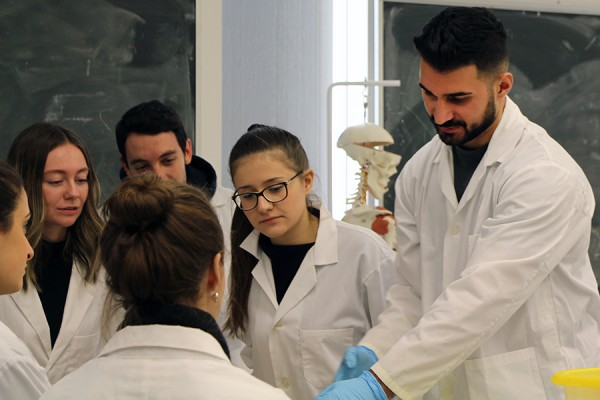 Biology students look on as teaching assistant Paul Bahnam conducts a tour through the human body.