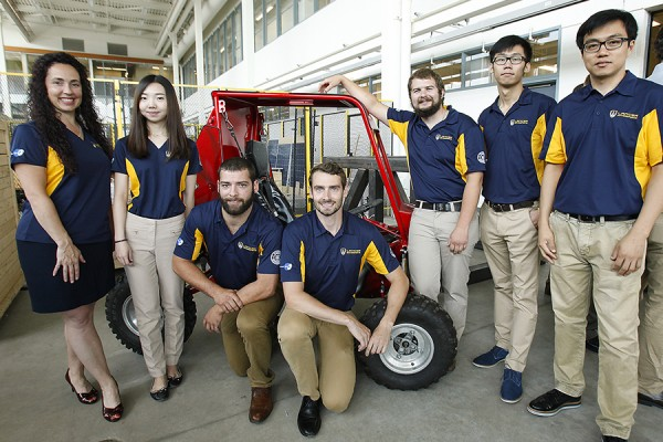 Members of the Lancer Motorsports team pose with their baja car capstone project.