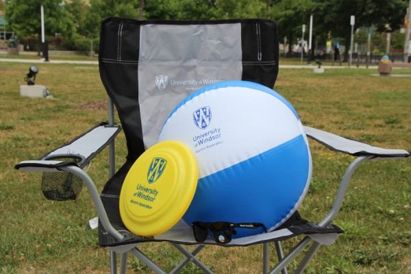 sunglasses, a toy flying disk, and an inflatable beachball balanced on folding lawn chair