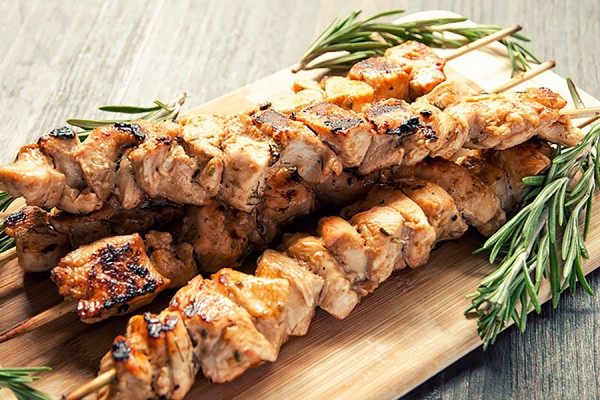 Skewers of grilled chicken souvlaki garnished with rosemary sprigs