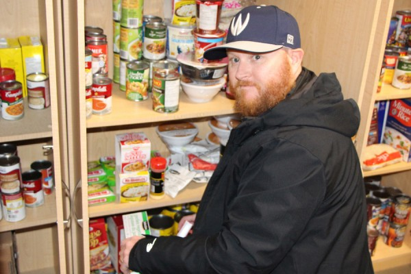 Chris Wainscott helps stock shelves in the Campus Food Bank