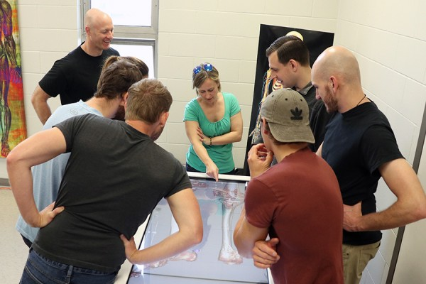 Human anatomy demonstrator Sara McNorton (centre) explains the virtual dissection table to medical staff of Cirque du Soleil.