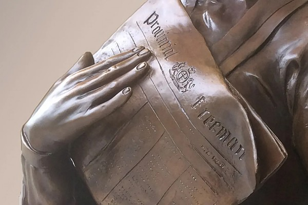 close-up of bronze hands holding Provincial Freeman newspaper