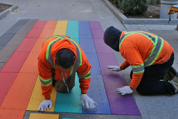 Contractors install Pride colours on the sidewalk outside Dillon Hall.