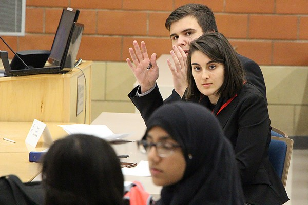 Students from Assumption and Massey high schools face off in debate Friday at the Odette School of Business.