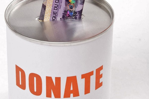 "hand depositing banknote into can marked ""Donate"""