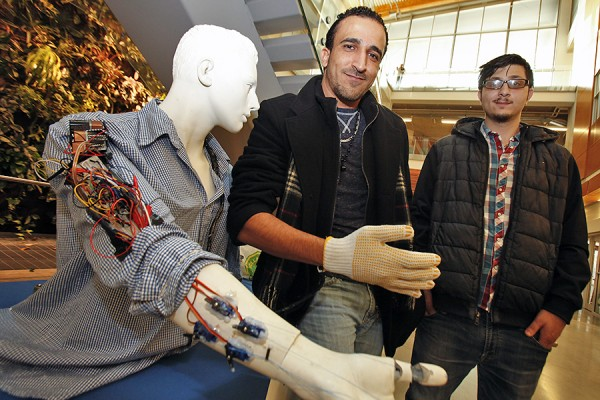 Engineering students Mohammad Kaddouh and Mohanad Elkafarneh demonstrate the robotic arm they designed and built.