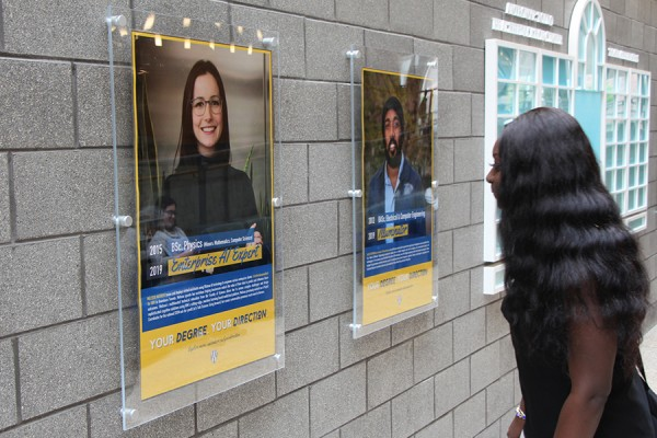 Esther Anim looks at some of the posters of alumni on display in the Toldo Health Education Centre.