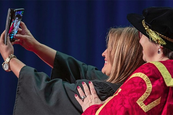 A happy grad poses for a selfie with chancellor Mary Jo Haddad.