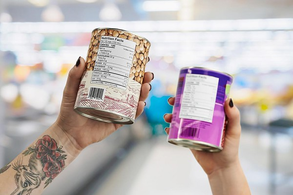hands holding canned goods to display nutrition labels