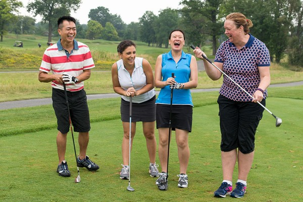foursome of golfers laughing
