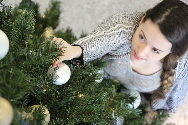 Jaz Zanier places an ornament on a Christmas tree