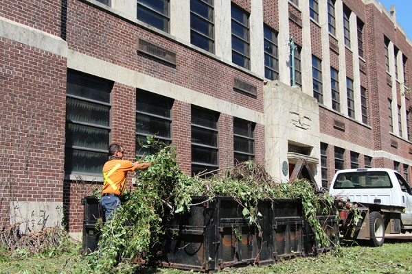 Groundskeeper Mike Mehenka clears ivy vines that had been removed from the exterior of Memorial Hall.