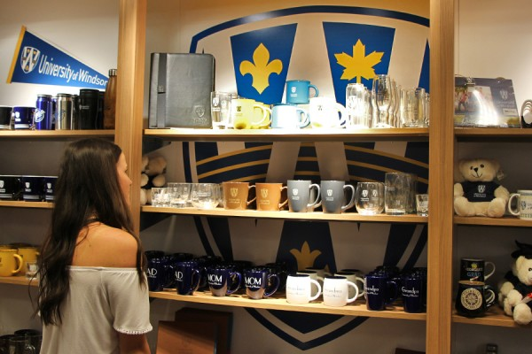 Third-year nursing student Nicole Preston admires some of the new UWindsor branded giftware available at the Campus Bookstore.