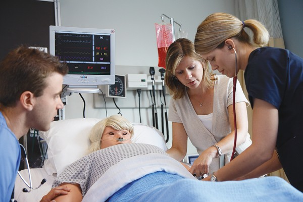 nursing professor working with students on patient simulator