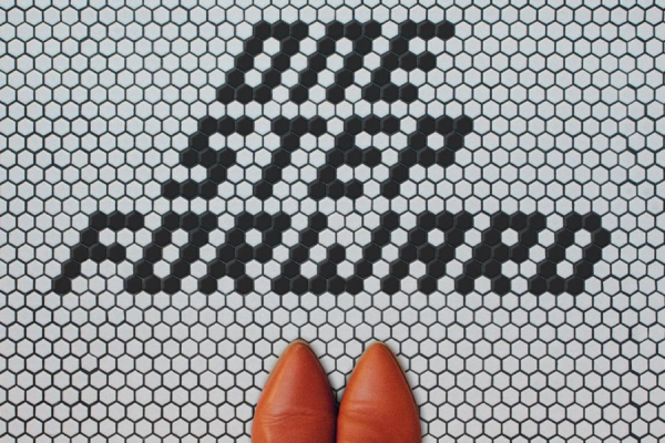"floor tiles spelling out ""One Step Forward"""