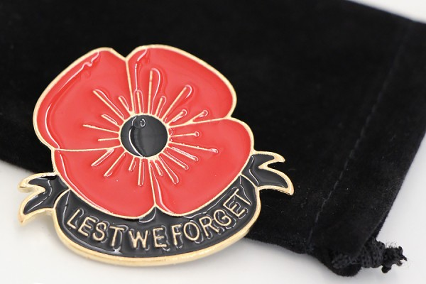 "enamel poppy pin with words ""Lest We Forget"""