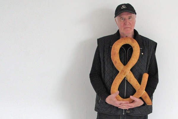 Iain Baxter& holding loaf of bread shaped as ampersand