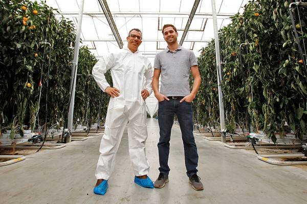 Rupp Carriveau and Lucas Semple pose inside greenhouse