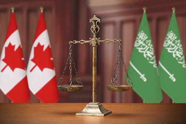 set of scales between flags of Canada and Saudi Arabia