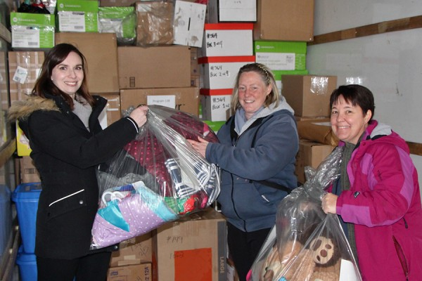 Sabina Howell, Lee Ann Davey, Tara Munro carry parcels into a truck