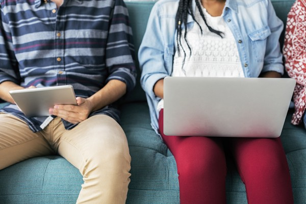 students holding laptop computers