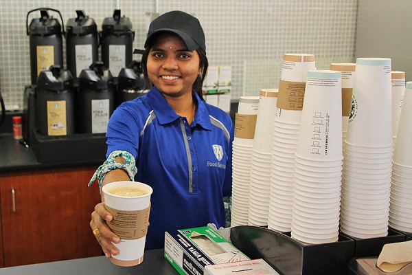 woman serving cup of Starbucks coffee