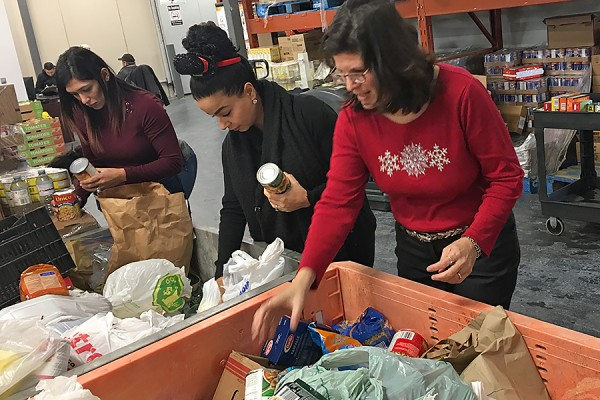 Selena Chauhan, Nour Hachem, and Linda DiPaolo sort donations to the Unemployed Help Centre as part of a community service learning experience.