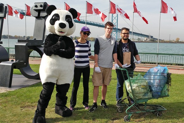 Students and a panda mascot pose with bags of litter.