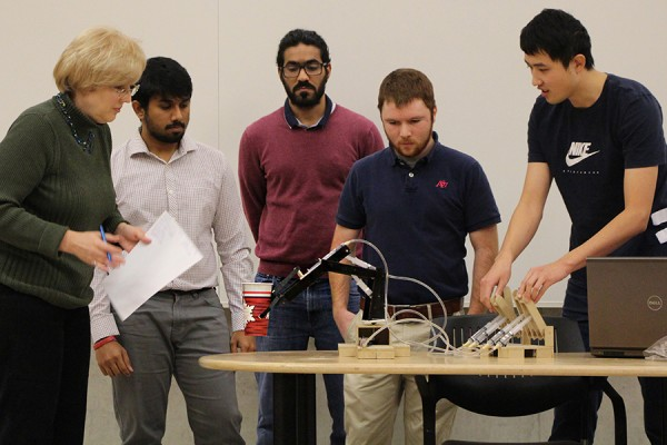 Professor Jill Urbanic looks on as students control a robotic arm to lift a paper cup during final project presentations Thursday in the Centre for Engineering Innovation.