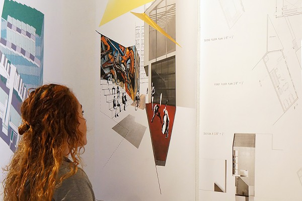 viewer takes in a work by student Max Pecoraro at the VABE exhibition
