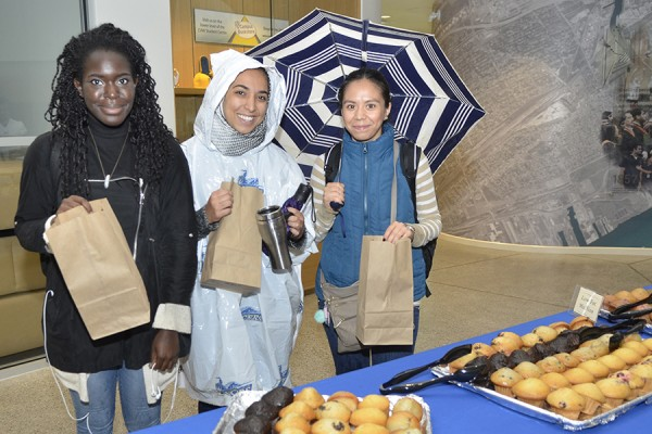 Students Vanessa Francis, Aicha Hassani, and Laura Cordovan pick up the makings of a continental breakfast marking the start of Alumni Weekend.
