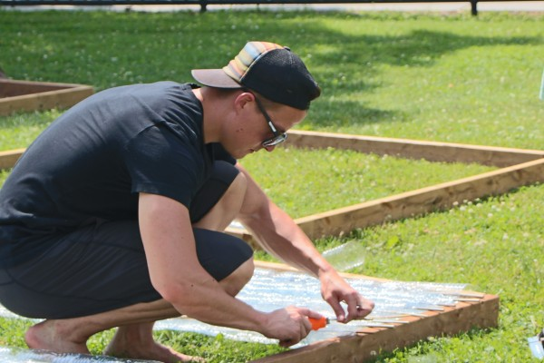 MBA student Connor Paterson worked with his team on building a green greenhouse made almost entirely of recyclable plastic water bottles, Monday, June 22.