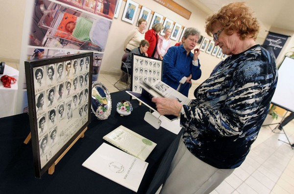 Shirley Whitfield flips through a year book during a ceremony to introduce the newly created digital archive of the Metropolitan General Hospital School of nursing archives at Windsor Regional Hospital. Photo credit: Tyler Brownbridge/The Windsor Star.