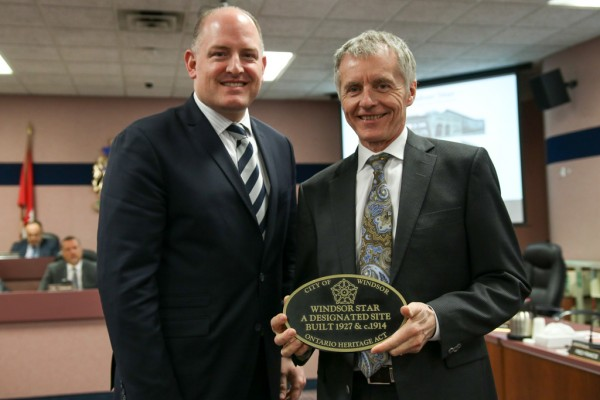 Windsor Mayor Drew Dilkens presents University of Windsor President Alan Wildeman with a heritage plaque for the rehabilitation of the former Windsor Star.