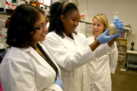 Sudipa Chatterjee, Pamela Ovadje and Carly Griffin examine a sample of the dandelion root extract.
