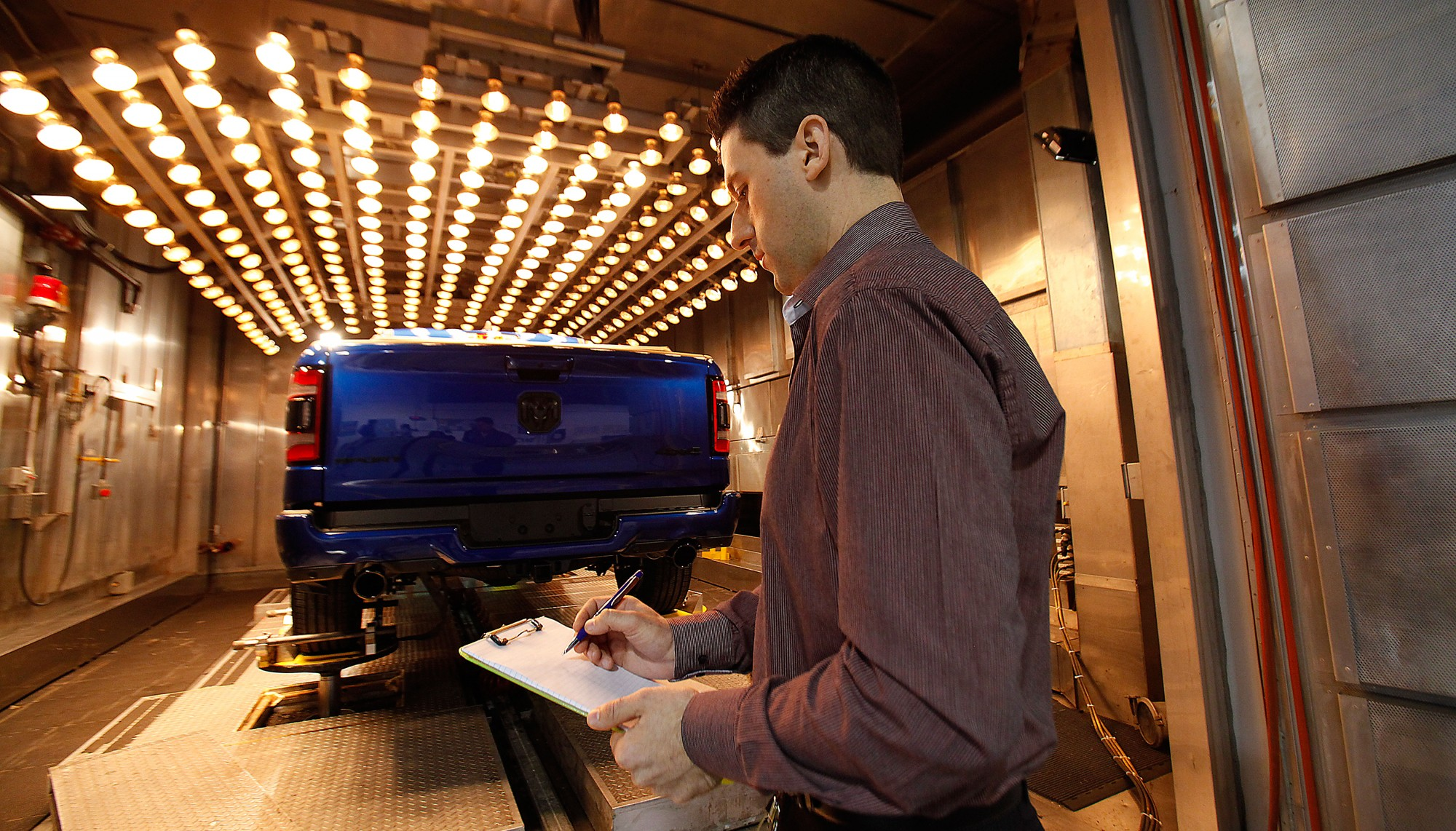A student examines a vehicle under heat testing lamps.