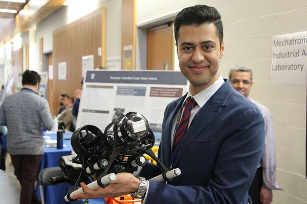 Doctoral student Faraz Talebpour shows off a remote-controlled underwater vehicle, one of the research projects displayed Friday in the Centre for Engineering Innovation.