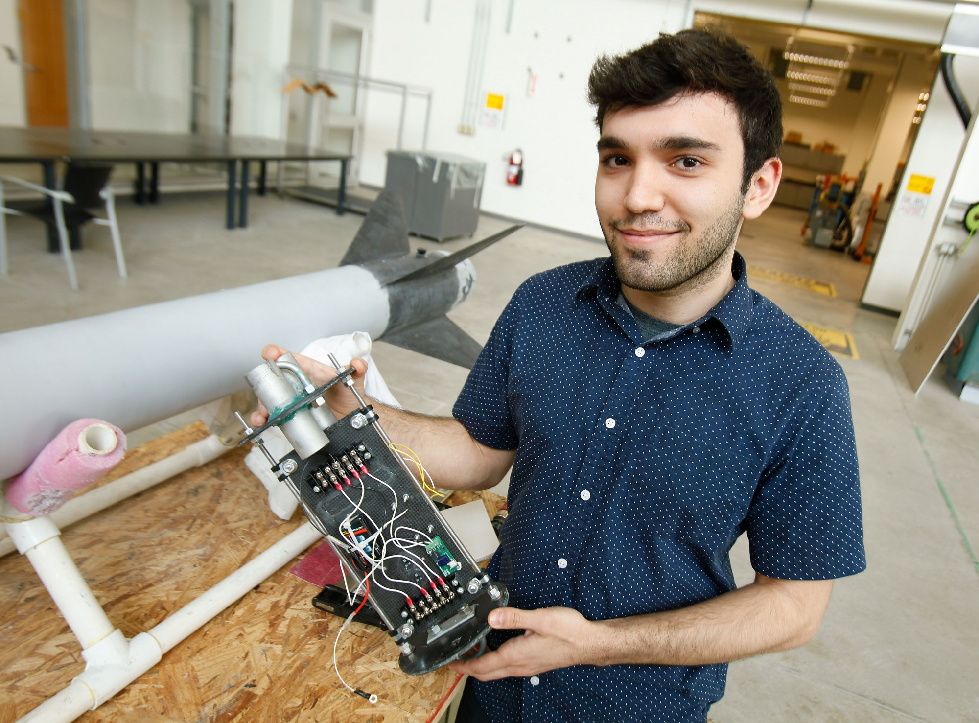 Aerospace student Atilla Saadat holds an avionics bay, which will log the altitude of a rocket