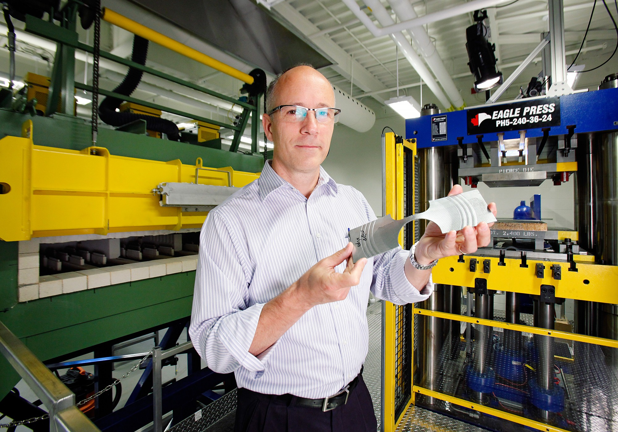 Dr. Daniel Green displays a sheet metal specimen in the Mechanical Testing Lab at the Ed Lumley Centre for Engineering Innovation. The specimen was stretch-formed in a formability test.