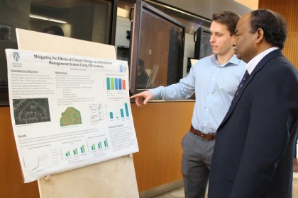 Civil engineering student Zach McPhee discusses measures to reduce stormwater run-off with professor Tirupati Bolisetti during a display of research posters Wednesday in the Centre for Engineering Innovation.