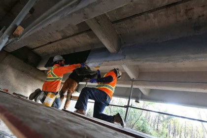 Luke Young, left, Cory Garno and Fabio Vaggio apply a new restoration method to the under side of a bridge on County Road 8 in Essex County on Nov. 14, 2016. TYLER BROWNBRIDGE / WINDSOR STAR