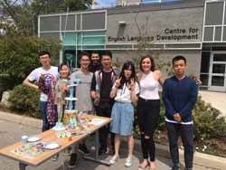 students posing alongside a tower they constructed