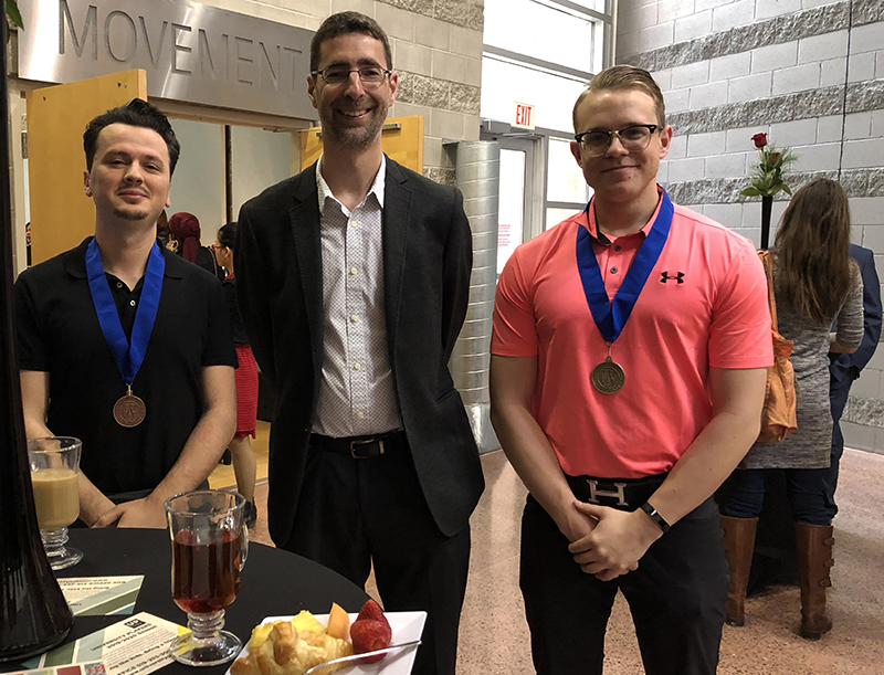 Gold Medallion recipient Mark McWhinney, double honours in Political Science and History with a minor in Greek & Roman Studies; and bronze medallion recipient Francesk Perpalaj, political science major, with Dr. John Sutcliffe, Political Science head.