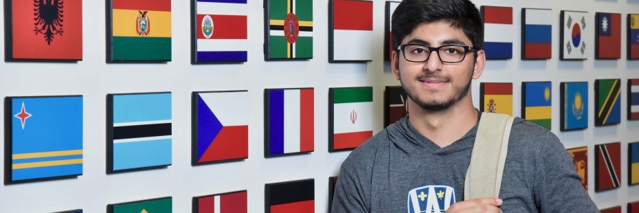 Male student standing in front of flags at International Student Centre