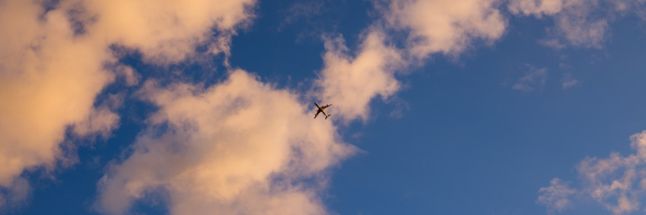 Photo of an airplane against a blue sky with white clouds