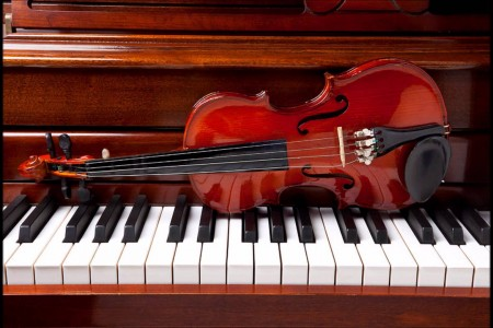 Image of a violin sitting on a piano